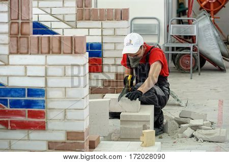 Tyumen Russia - February 17. 2017: Open championship of professional skill among youth World skills Russia Tyumen - 2017. Young bricklayer performs a task of competition of professionals