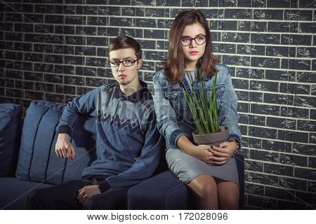 Shy and serious teen couple, wearing glasses, sitting in front of brick wall. Hipster style young man and girl, holding house plant.