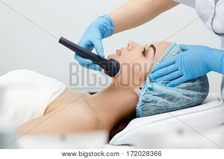 Hypersonic Phonophoresis. Model and doctor. Cosmetological clinic, procedure. Profile, close-up Healthcare clinic cosmetology