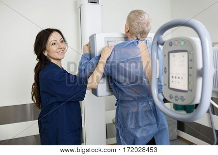 Happy Radiologist Taking Xray Of Man In Hospital