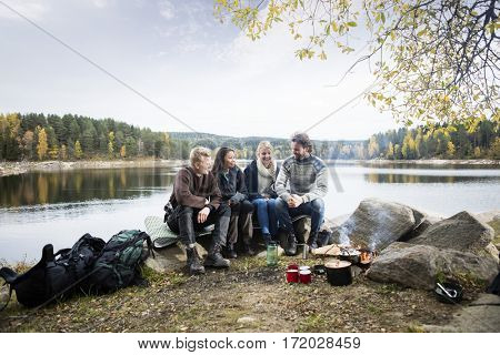 Friends Sitting On Lakeshore During Camping