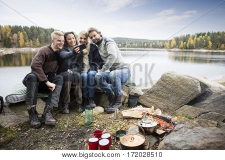 Friends Taking Self Portrait At Lakeside Camping