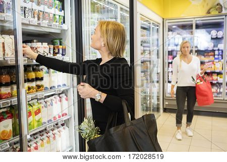 Woman Choosing Juice Packets In Grocery Store