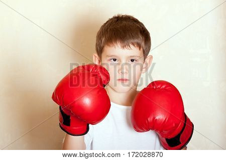 Portrait of a boy in red boxing gloves closeup
