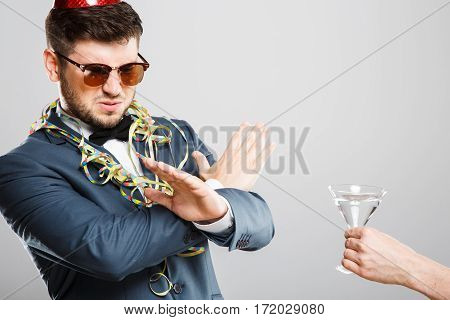 Man in suit with bow and sunglasses. Don't want martini, passes up, disguise, hands crossed. B-day hat, confetti. Outrageous, fancy look, cool. Waist up, studio indoors