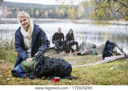 Young Woman Unpacking Backpack At Campsite