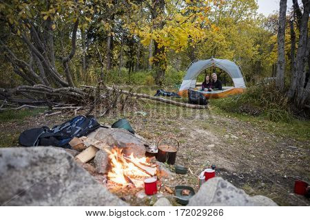 Campfire With Couple Relaxing In Tent At Forest