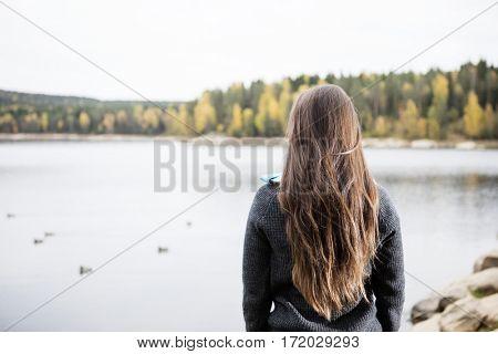 Rear View Of Young Woman Enjoying Lake View