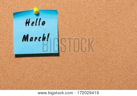 Hello March - Note With Text pinned at cork notice board. With empty space. Spring begin concept.