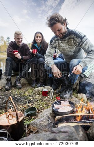 Man Cooking Food On Campfire With Friends In Background