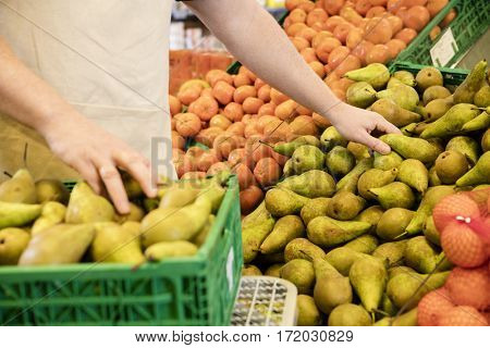 Midsection Of Salesman Arranging Fresh Pears