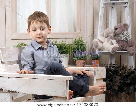 Pensive little boy. Bright children's room. Portrait of a child