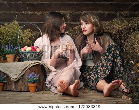 Young girls peasant briskly communicate. Basket with Easter eggs. Warped. Old house bouquets of dried flowers