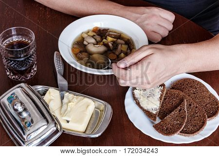 Man Eating Soup With His Left Hand. Mushroom . Bread. Butter.