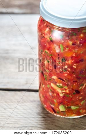 Jar of salsa on the wooden background