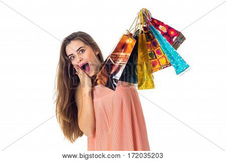 Merry girl keeps a hand near the mouth and in the second hand raised different bright bags isolated on white