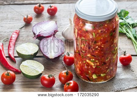Jar of salsa with ingredients on the wooden background