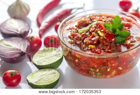 Bowl of salsa with ingredients on the white background
