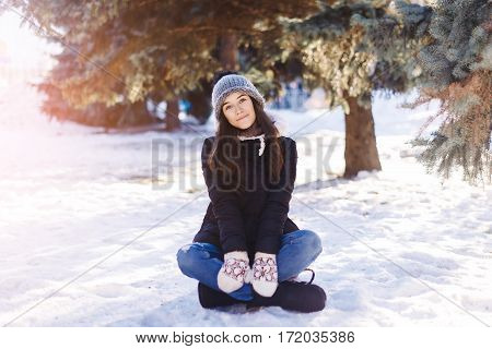 Beautiful Young Girl Sits On To Snow In Warm Clothes In Winter Outdoors
