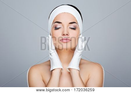 Woman with white headband touching face with both hands in white gloves. Model with closed eyes. Head and shoulders. Beauty salon, studio, indoors, grey background