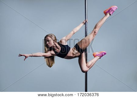 Young slim pole dance woman on blue background