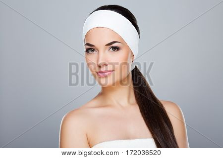 Woman with white headband and ponytail. Model looking at camera, ponytail hanging from the shoulder. Head and shoulders. Beauty salon, studio, indoors, grey background