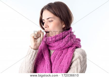 a young girl in a warm scarf stands sideways and coughs isolated on white