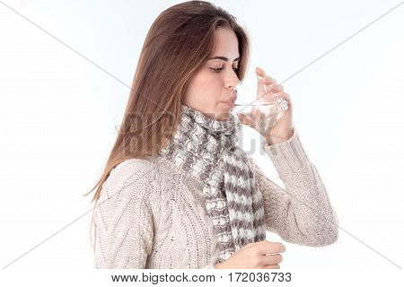 girl in a warm sweater stands sideways and drinking a glass of water isolated on white