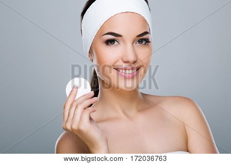 Woman with white headband holding cotton pad. Model looking at camera and smiling, head and shoulders, closeup. Beauty salon, studio, indoors, grey background