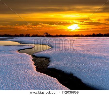 Sunset over brook across winter meadow