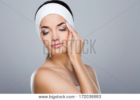 Woman with white headband touching her face with cotton pad. Model with closed eyes and light smile, head and shoulders. Beauty salon, studio, indoors, grey background
