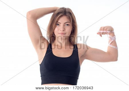 close-up of a beautiful slender athletic girl who is smiling and showing his biceps hand and the other hand holding his head