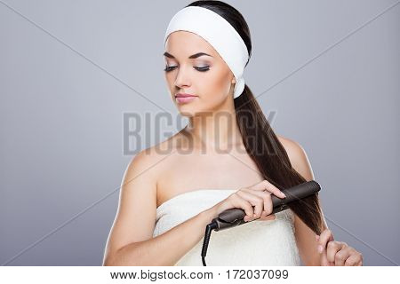 Young woman with white headband straightening her ponytail with hair straightener. Looking aside and down. Studio, indoors, waist up, grey background