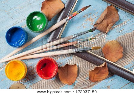 Paint brushes, paint, frame and dry leaves