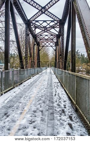 Snow covers a bridge and trestle that spans the Cedar River in Renton Washington.