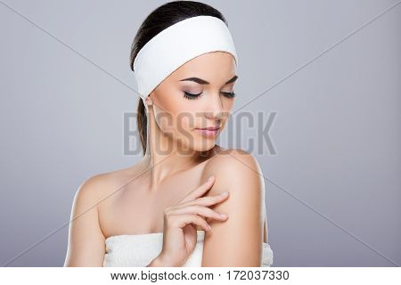 Young woman with white headband touching her shoulder. Looking aside and down. Studio, indoors, head and shoulders, grey background