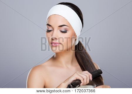 Young woman with white headband straightening her ponytail with hair straightener. Looking aside and down. Studio, indoors, head and shoulders, grey background