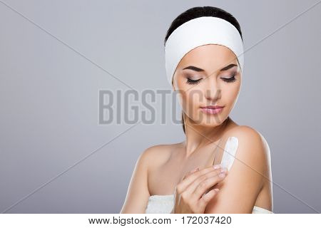 Young woman with white headband  putting cream on her shoulder. Looking aside and down. Studio, indoors, head and shoulders, grey background