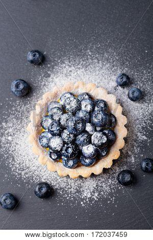 Blueberry tart pie tart with vanilla custard. Slate stone background. Top view Copy space