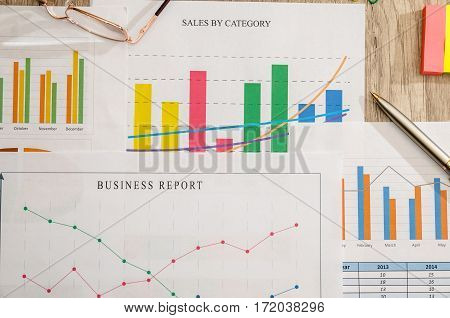business report with pen on desk close up