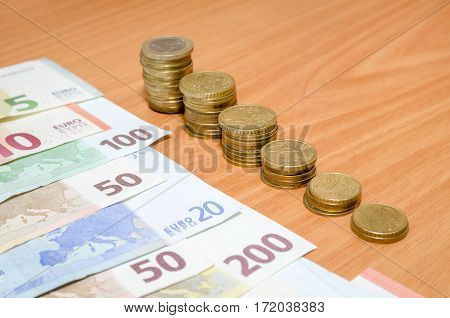 euro banknote and coins on wooden table