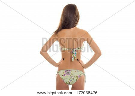 slim brunette woman with beautiful round buttocks in swimsuit with floral pattern posing from behind isolated on white