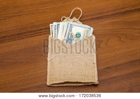 Dollars Of Different Values In Sack  On Table