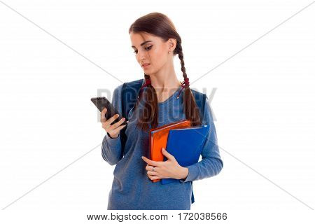 sad smart student girl with backpack on her shoulders and folder for notebooks in her hands looking at mobile phone isolated on white