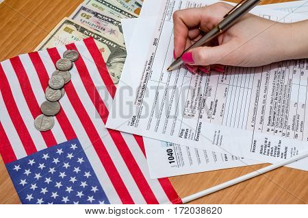 Business Woman Fills The Tax Form 1040 With Money, Pen, Flag Of Usa And Calculator