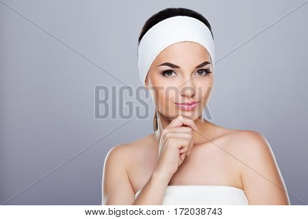 Young woman with white headband thinking about something and smiling ironically. Rubbing chin. Looking at camera. Studio, indoors, grey background. Beauty care