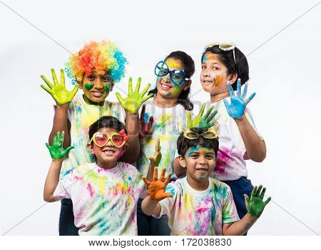 5 indian small kids / friends / siblings celebrating Holi festival holding gulal thali having copy space, isolated over white background standing in one line
