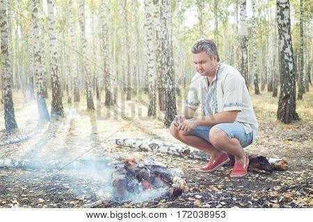Man sitting next to bonfire in the birch grove. Man in Ukrainian vyshyvanka.