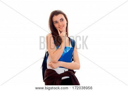 cheerful smart student girl in brown sport clothes with backpack on her shoulders smiling and looking away isolated on white