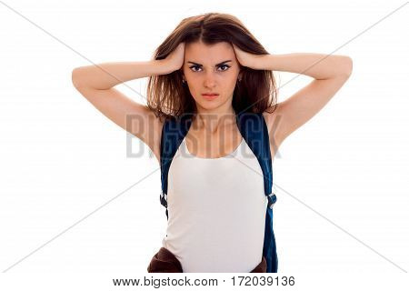 anfry smart student girl in brown sport clothes with backpack on her shoulders looking at the camera with hands on her head isolated on white